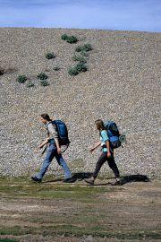 Walkers trudge beside a shingle embankment on the Norfolk Coast Path.
